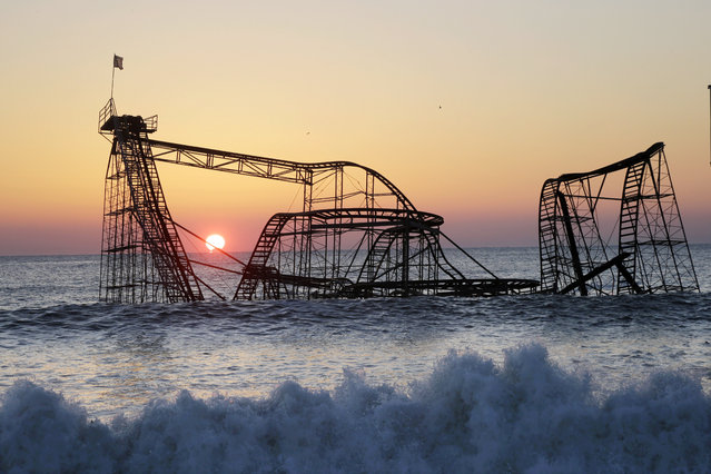 The sun rises in Seaside Heights, N.J., Monday, February 25, 2013, behind the Jet Star Roller Coaster which has been sitting in the ocean after part of the Funtown Pier was destroyed during Superstorm Sandy. (Photo by Mel Evans/AP Photo)