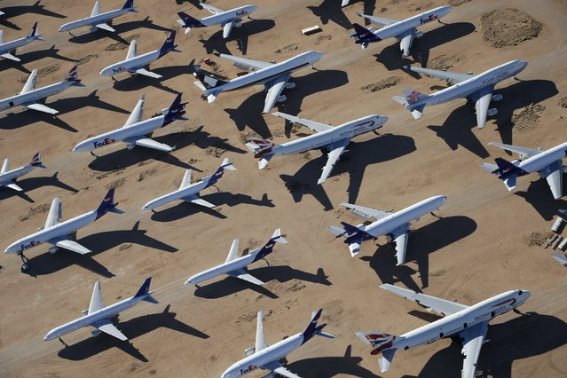 Old airplanes, including British Airways and China Airlines Boeing 747-400s and FedEx planes, are stored in the desert in Victorville, California, March 13, 2015. Last year, there were zero orders placed by commercial airlines for new Boeing 747s or Airbus A380s, reflecting a fundamental shift in the industry toward smaller, twin-engine planes. (Photo by Lucy Nicholson/Reuters)