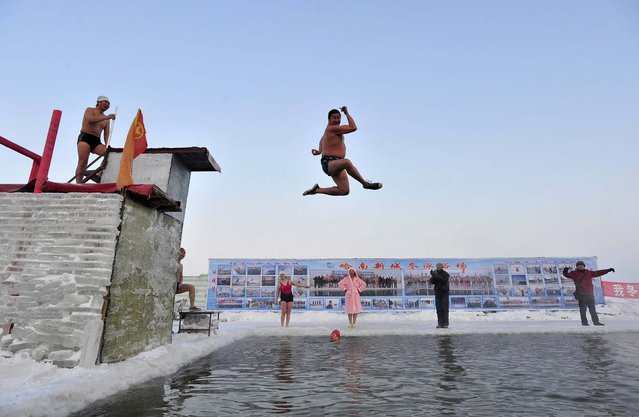 A winter swimmer gestures as he jumps into the icy water of the partially frozen Songhua River in Harbin, China, on December 28, 2013. The temperature in Harbin on Saturday reached as low as minus 5.8 degrees Fahrenheit (– 14.5 °C). (Photo by Sheng Li/Reuters)