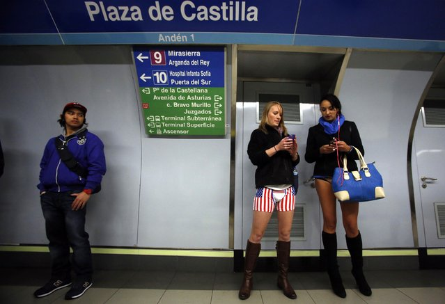 """Passengers without their pants check their mobile phones as they wait for a train during the """"No Pants Subway Ride"""" event at Plaza de Castilla subway station in Madrid January 12, 2014. (Photo by Sergio Perez/Reuters)"""