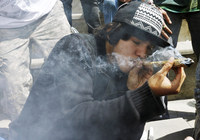 Partygoers listen to music and smoke marijuana on one of several days of the annual 4/20 marijuana festival, in Denver's downtown Civic Center Park, Saturday April 18, 2015. (Photo by Brennan Linsley/AP Photo)