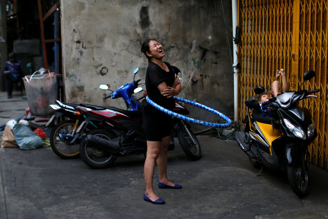 A woman plays with a hula hoop outside her house in Chinatown, Bangkok, Thailand January 24, 2017. (Photo by Jorge Silva/Reuters)
