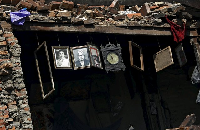 Framed photographs and a clock are seen hanging inside a damaged house after Saturday's earthquake in Bhaktapur, Nepal April 27, 2015. (Photo by Adnan Abidi/Reuters)