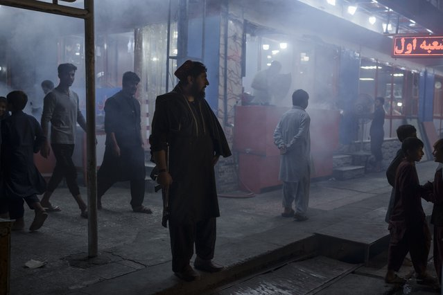 A Taliban fighter stands in the corner of a busy street at night in Kabul, Afghanistan, Friday, September 17, 2021. (Photo by Felipe Dana/AP Photo)