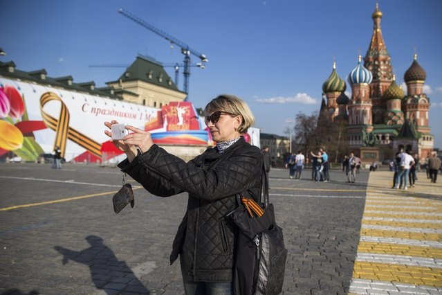 A woman with St. George ribbon, a symbol of the Soviet participation in the World War II,  on a handbag, takes a selfie, with St. Basil Cathedral in the background, in Red Square in Moscow, Russia, Tuesday, April 28, 2015. The Victory Day military parade to celebrate 70th anniversary of the victory in WWII, will be held in Red Square on May 9. (Photo by Pavel Golovkin/AP Photo)