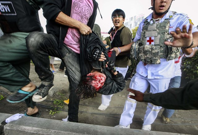 A suspected gunman, center, is carried by a medic official, right, and anti-government protesters to an ambulance shortly after he was caught and beaten after firing a pistol to protesters, wounding one during a rally outside the Army Club in Bangkok, Thailand, on January 28, 2014. Thailand's Prime Minister Yingluck Shinawatra met Tuesday with the country's polling body to discuss the possibility of postponing a general election set for this weekend, even as protesters tried to disrupt the talks. (Photo by Wason Wanichakorn/Associated Press)
