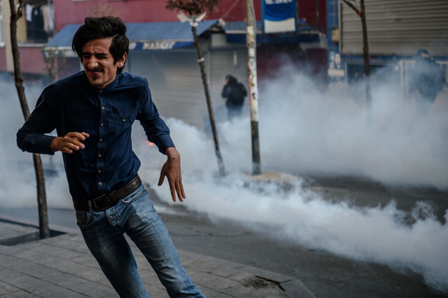 People run away from tear gas fired by Turkish anti-riot police on March 11, 2016 at Okmeyani district in Istanbul as people gather to mark the second anniversary of the death of the youngest victim of the Gezi Park protests. Berkin Elvan was 14-years-old when he was hit by a police teargas cannister in Istanbul on June 16, 2013, as anti-government demonstrations swept Turkey. (Photo by Ozan Kose/AFP Photo)