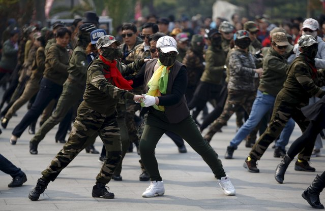 Women dressed in military style clothes perform square dancing at a park square in Beijing, China, April 9, 2015. (Photo by Kim Kyung-Hoon/Reuters)