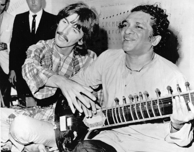 Beatle George Harrison, left, sits cross-legged with musical mentor Ravi Shankar of India, a sitar virtuoso, in Los Angeles, USA, August 4, 1967. Harrison is being taught by Shankar how to play the sitar. (Photo by AP Photo)
