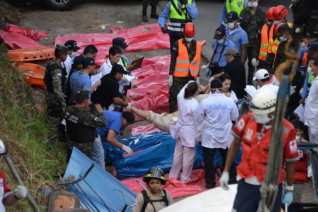 Police, firefighters and Red Cross members rescue corpses after a bus and a truck crashed on the road that links the Honduran capital with the south of the country, near Germania, 11 km south of Tegucigalpa on February 5, 2017. (Photo by Orlando Sierra/AFP Photo)