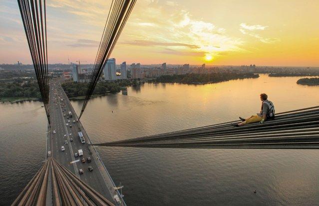 One of Yaroslav Segeda's friends climbs the Moscow Bridge in Kiev. (Photo by Yaroslav Segeda/Solent News)