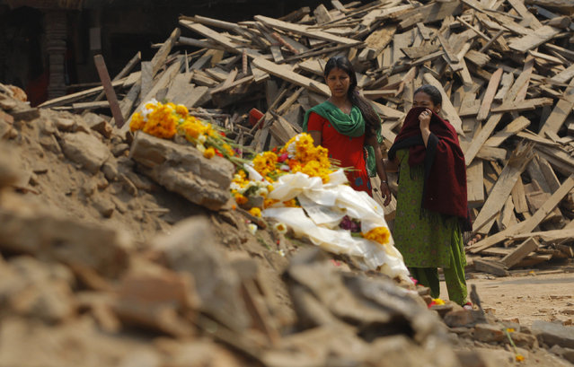 Nepalese women look at floral tributes placed in memory of victims killed in last week's earthquake, at  Basantapur Durbar Square in Kathmandu, Nepal, Thursday, May 7, 2015. (Photo by Niranjan Shrestha/AP Photo)