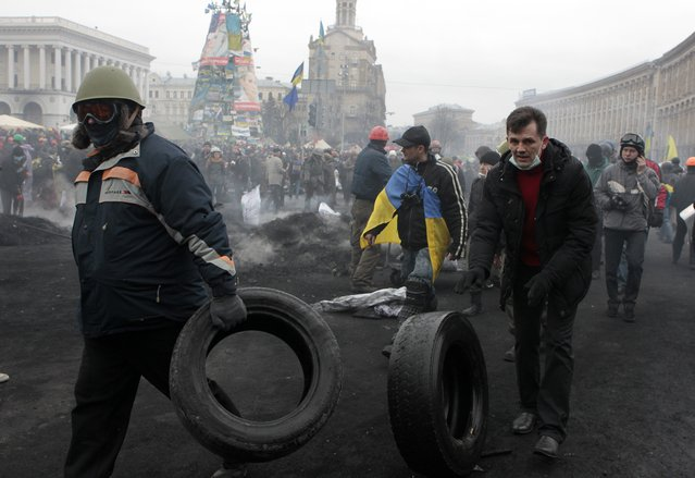 Activists carry car tires in Kiev's Independence Square, the epicenter of the country's current unrest, Thursday, February 20, 2014. (Photo by Sergei Chuzavkov/AP Photo)