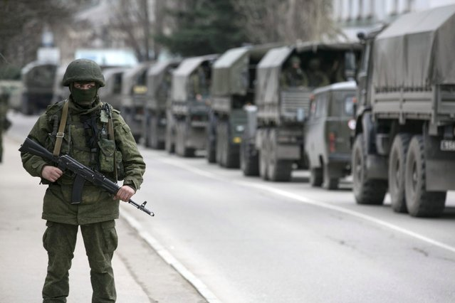 An armed serviceman stands near Russian army vehicles outside a Ukrainian border guard post in the Crimean town of Balaclava March 1, 2014. (Photo by Baz Ratner/Reuters)