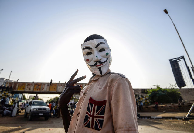 A Sudanese protester wears a Guy Fawkes mask outside the army headquarters in Khartoum on May 6, 2019. Defiant Sudanese protesters broke their fast on the first day of Ramadan today with chicken soup and beans, vowing to press on with their campaign for a civilian rule. As the call for the evening Maghreb prayer echoed, crowds of protesters gathered at the sit-in area in central Khartoum for iftar after a day of sweltering heat, an AFP correspondent reported. (Photo by Mohamed el-Shahed/AFP Photo)