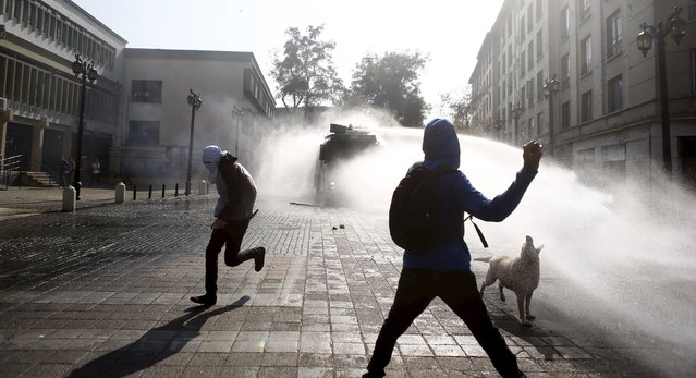 Protesters clash with riot police during a demonstration to demand changes in the education system at Santiago, May 14, 2015. (Photo by Ivan Alvarado/Reuters)