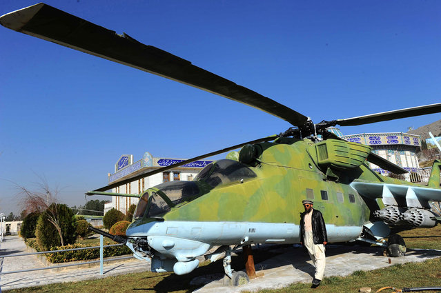 Museum assistant Sheikh Abdullah stands alongside a Soviet helicopter outside the Jihad Museum in Herat, on February 15, 2014. (Photo by Aref Karimi/AFP Photo via The Atlantic)