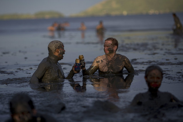"""Two men beer toast while wading in mud during the traditional """"Bloco da Lama"""" or """"Mud Street"""" carnival party, in Paraty, Brazil, Saturday, February 25, 2017. Legend has it the """"bloco"""" was born in 1986 after local teens hiking in a nearby mangrove forest smeared themselves with mud to discourage mosquitoes and then wandered through Paraty. The party grew year after year, but revelers eventually were banned from parading in the colonial downtown after shopkeepers complained pristine white walls were stained with the hard-to-remove mud. (Photo by Mauro Pimentel/AP Photo)"""