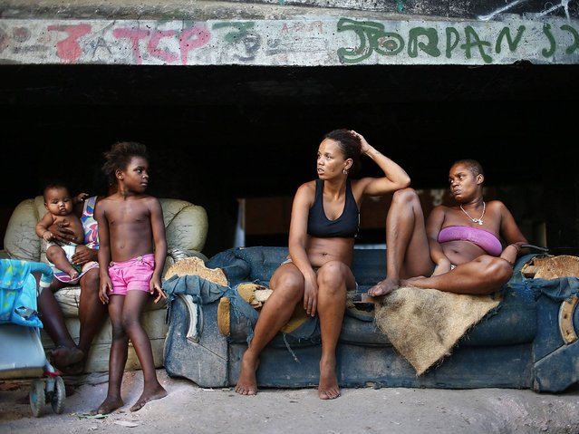 "Residents (R to L) Luiza, Janubie, Leiticia and Lucas sit beneath an overpass near their houses in an impoverished area in the unpacified Complexo da Mare slum complex, one of the largest ""favela"" complexes in Rio de Janeiro. (Photo by Mario Tama/Getty Images)"