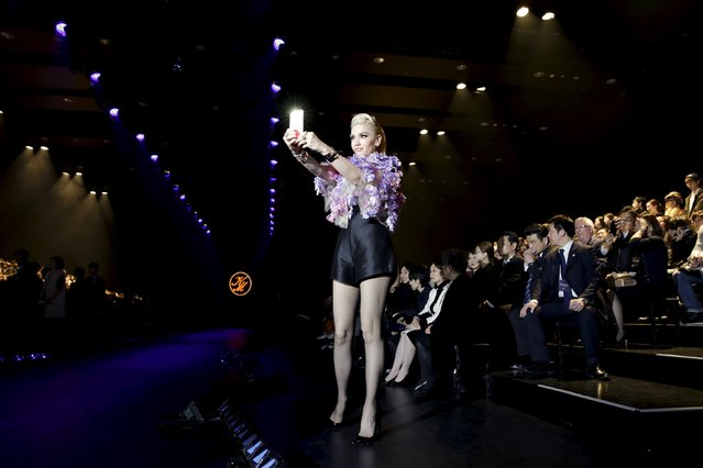 U.S. singer-songwriter Gwen Stefani takes pictures of the media before a fashion show by Keita Maruyama of his Autumn/Winter 2016 collection during Tokyo Fashion Week in Tokyo, Japan, March 14, 2016. (Photo by Thomas Peter/Reuters)