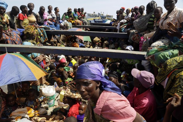 Refugees who fled Burundi's violence and political tension sing in a speedboat taking them to a ship freighted by the UN, at Kagunga on Lake Tanganyika, Tanzania, Saturday, May 23, 2015 to be taken to the port city of Kigoma. (Photo by Jerome Delay/AP Photo)