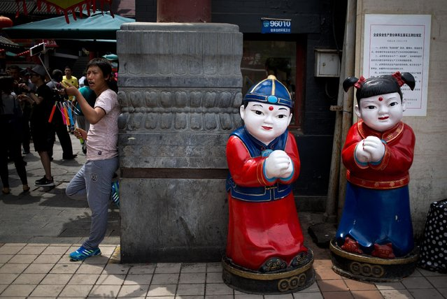 A man sells selfie sticks near a pair of statue at the Wangfujing shopping district in Beijing, China Thursday, May 21, 2015. (Photo by Andy Wong/AP Photo)