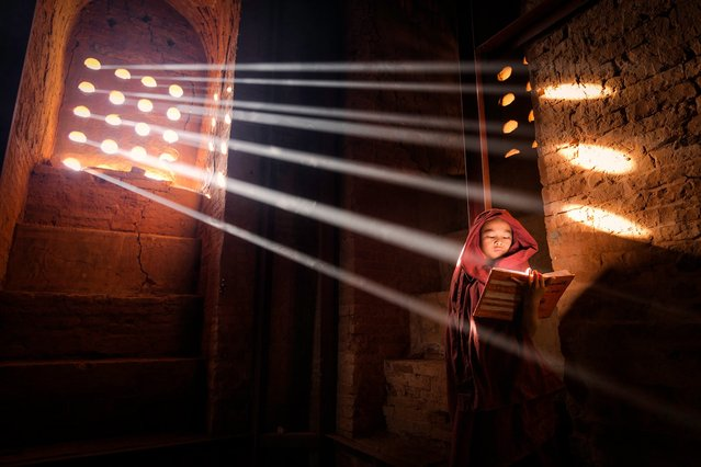"""""""Light Source"""". Young Monk finds a perfect light source to read his book inside of his pagoda – Old Bagan, Burma. (Photo and caption by Marcelo Castro/National Geographic Traveler Photo Contest)"""