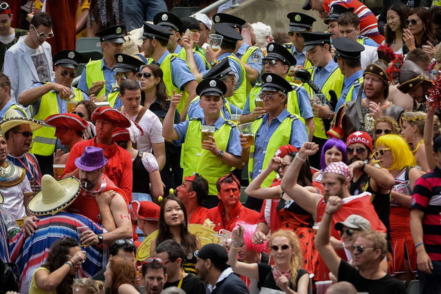 Rugby fans wearing policemen costumes (C) drink beer at the rugby sevens tournament in Hong Kong on March 29, 2014. (Photo by Philippe Lopez/AFP Photo)