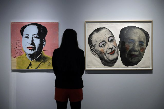 "A British Museum representative poses for photographs next to Andy Warhol's ""Mao"", left, and Jim Dine's ""Drag: Johnson and Mao"" which feature in ""The American Dream: pop to the present"" exhibition during a media photocall at the British Museum in London, Monday, March 6, 2017. (Photo by Matt Dunham/AP Photo)"