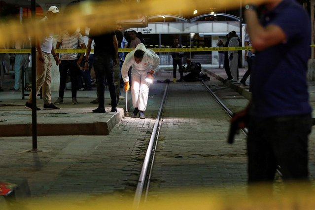 Onlookers gather at the scene outside a metro station where a man reportedly wearing an explosive belt blew himself up in the early hours of July 3, 2019 in the capital Tunis, after being chased by police. The Tunisian interior ministry said a jihadist, on the run for two days, was killed on July 3 in the western Tunis neighbourhood of Cité Intilaka while security forces were chasing him to detain him. The official sources said the suspect blew himself up during the police operation. (Photo by Zoubeir Souissi/Reuters)