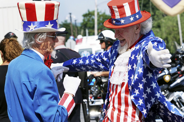 Uncle Sams Fred Polnisch and Gordon Dunham greet each other before the Fourth of July Parade, in Pittsfield, Massachusetts on July 4, 2019. (Photo by Ben Garver/The Berkshire Eagle via AP Photo)