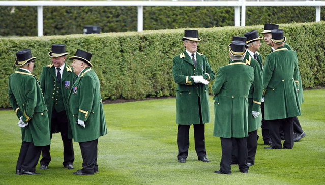 Gatekeepers stand in the paddock before having a photo taken before the second day of  Royal Ascot horse racing meet at Ascot, England, Wednesday, June 17, 2015. Royal Ascot is the annual five day horse race meeting that Britain's Queen Elizabeth II attends every day of the event.(AP Photo/Alastair Grant)