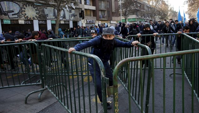 Protesters push police barriers during a protest to demand changes in the Chilean education system in Santiago, Chile June 25, 2015. (Photo by Marcos Brindicci/Reuters)