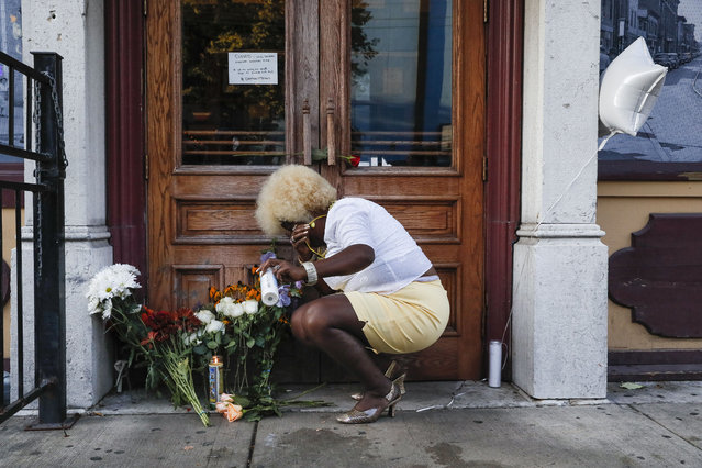 Mourners place flowers and candles at the front of Ned Peppers bar while they gather at the scene of a mass shooting before a prayer vigil, Sunday, August 4, 2019, in Dayton, Ohio. Multiple people in Ohio have been killed in the second mass shooting in the U.S. in less than 24 hours, and the suspected shooter is also deceased, police said. (Photo by John Minchillo/AP Photo)