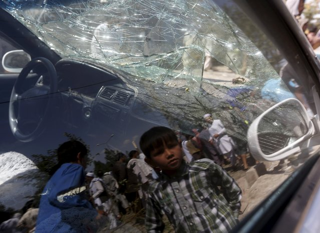 An Afghan boy is reflected on the window of a damaged vehicle at the site of a car bomb in Kabul, Afghanistan, June 30, 2015. (Photo by Omar Sobhani/Reuters)