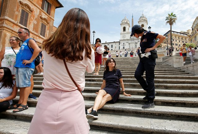 A municipal policewoman asks a tourist to rise from Rome's Spanish step, after the city's municipality banned sitting down on the famed stairs, in Rome, Italy, August 8, 2019. (Photo by Remo Casilli/Reuters)