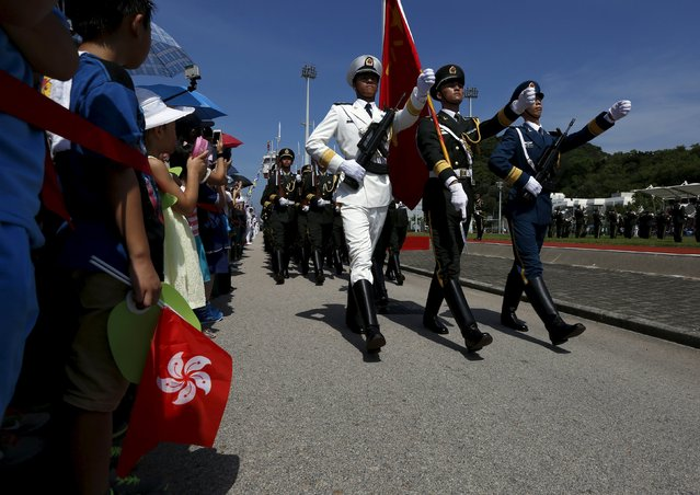 People's Liberation Army (PLA) soldiers march past a visitor holding a Hong Kong flag at a PLA naval base in Hong Kong, China July 1, 2015. (Photo by Bobby Yip/Reuters)