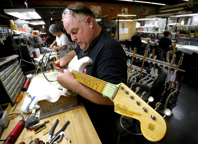 A finished Fender Stratocaster is adjusted by Kenneth Maas in the Fender Custom Shop in Corona, Calif. on Tuesday, October 15, 2013. Leo Fender developed the instrument in a small workshop in Fullerton, Calif. six decades ago. (Photo by Matt York/AP Photo)