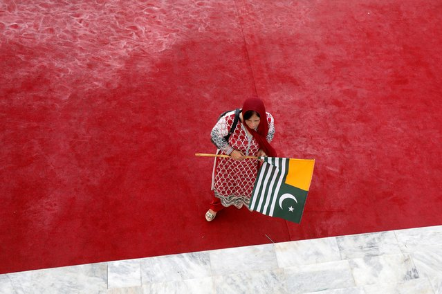 A woman walks with a Kashmir's flag to express solidarity with the people of Kashmir, during a ceremony to celebrate Pakistan's 72nd Independence Day at the Mausoleum of Muhammad Ali Jinnah in Karachi, Pakistan on August 14, 2019. (Photo by Akhtar Soomro/Reuters)