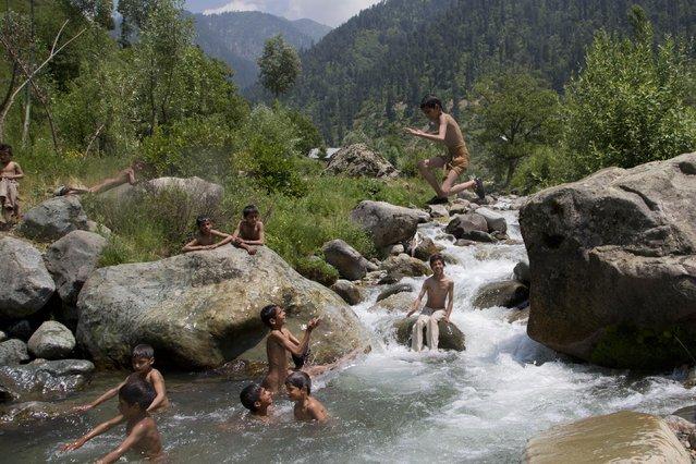 A Kashmiri boy jumps into a stream as boys cool off on a hot afternoon near Wangath, Some 48 kilometers (30 miles) northwest of Srinagar, Indian controlled Kashmir, Sunday, July 5, 2015. (Photo by Dar Yasin/AP Photo)