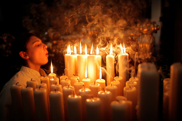 """A penitent of """"Lagrimas and Favores"""" blows out candles inside a church as she takes part in a Palm Sunday procession, marking the start of the Holy Week in Malaga, southern Spain, April 9, 2017. (Photo by Jon Nazca/Reuters)"""