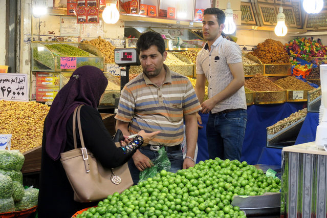 A shopkeeper helps a woman in a shop selling nuts near Tehran's Grand Bazaar, Iran May 2, 2016. (Photo by Marius Bosch/Reuters)