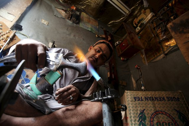 A man works in his shop at a marketplace in the old quarter of Sanaa, Yemen during the holy month of Ramadan July 11, 2015. (Photo by Mohamed al-Sayaghi/Reuters)