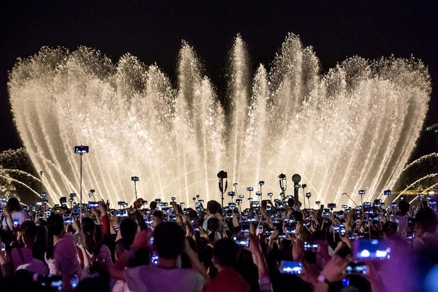 People record a water fountain show with their mobile phones in Hangzhou, Zhejiang province, China May 1, 2016. (Photo by Chance Chan/Reuters)