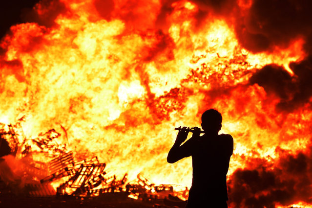 Iain McFarland, an Orange bandsman, plays his flute during the 11th night bonfire at the New Mossley housing estate on July 12, 2015 in Belfast, Northern Ireland. New Mossley is widely recognised as the largest bonfire in the province. (Photo by Charles McQuillan/Getty Images)