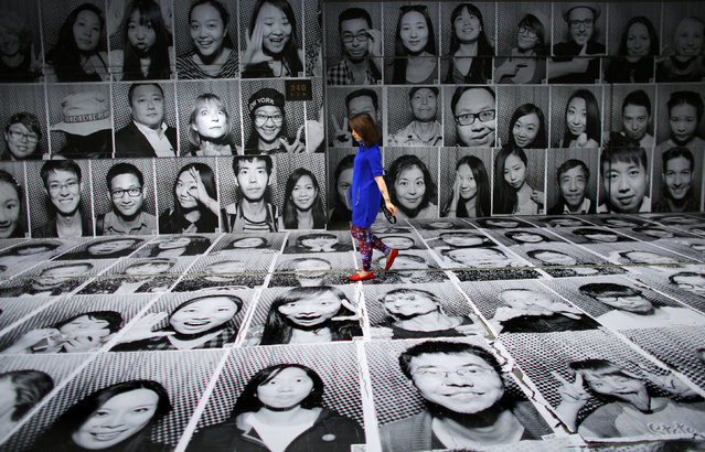 A woman walks through a display of portraits which were made as part of the Inside Out art project by French artist JR at Xintiandi area in downtown Shanghai May 14, 2014. JR and his team set up a photo studio and printing equipment in a truck to capture portraits of locals and tourists, which are then displayed in public. The portraits will be pasted on walls in the Lakeside Road area in Xintiandi. (Photo by Carlos Barria/Reuters)