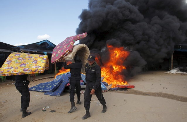 Police burn mattresses during an operation to destroy illegal gold mining camps in a zone known as Mega 14, at the southern Amazon region of Madre de Dios, July 13, 2015. Production from wildcat miners in Madre de Dios, who sell their ore up the supply chain, made up about 10 percent of national production before President Ollanta Humala launched the harshest crackdown yet on illegal gold mining last year. (Photo by Janine Costa/Reuters)