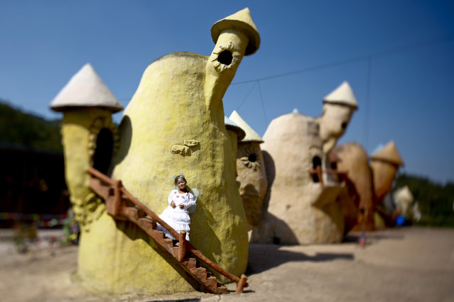 "A picture made with a tilt-shift lens shows ""Dwarf Empire"" cast member 19-year-old Han Zhen Yan posing in her fairy costume backstage outside one of the fairy tale-like houses at the Dwarf Empire theme park outside Kunming, China's Yunnan province, 04 April 2013. (Photo by Diego Azubel/EPA)"