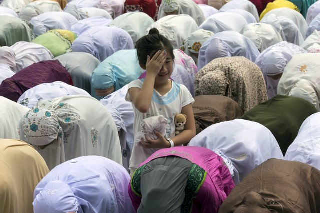 A girl reacts as Indonesian Muslim women working in Hong Kong, pray during Eid al-Fitr at Victoria Park in Hong Kong, China July 18, 2015. (Photo by Tyrone Siu/Reuters)
