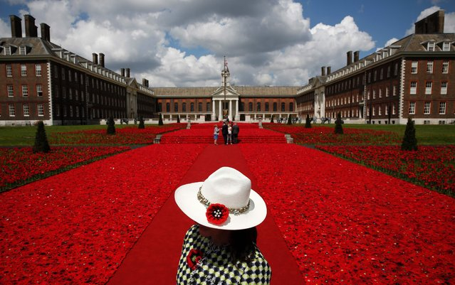 """A volunteer stands to the entrance of the 5000 Poppies Garden at the Chelsea Flower Show in London on May 23, 2016, the garden, created by Australians Lynn Berry and Margaret Knight is a tribute to their fathers who both fought in WWII. The Chelsea flower show, held annually in the grounds of the Royal Hospital Chelsea, will run this year from May 24-28. Britain has a """"lost generation"""" with no gardening skills, the Royal Horticultural Society warned on Monday, as its sprawling Chelsea Flower Show got under way with an inauguration by Queen Elizabeth II. (Photo by Adrian Dennis/AFP Photo)"""